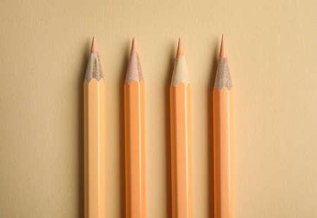 Composition à plat avec des crayons de couleur sur fond beige