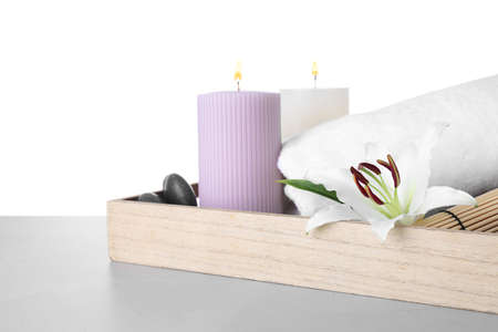 Tray with flower and spa supplies on marble table against white background
