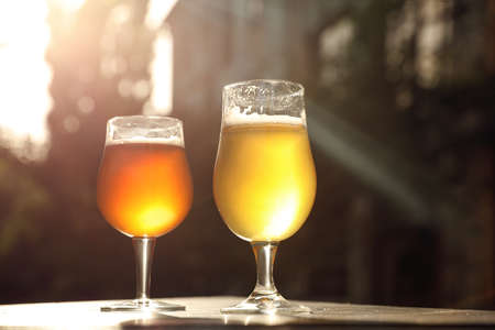 Glasses of cold tasty beer on wooden table outdoors Imagens