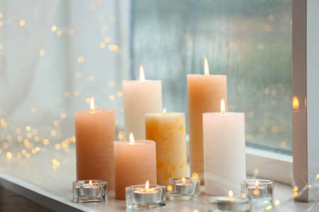 Beautiful burning candles and fairy lights at windowsill on rainy day Banque d'images