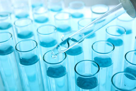 Dropping sample into test tube with light blue liquid, closeup 写真素材