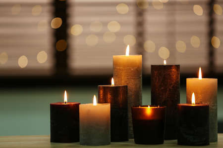 Beautiful burning candles on wooden table against festive lights. Space for text