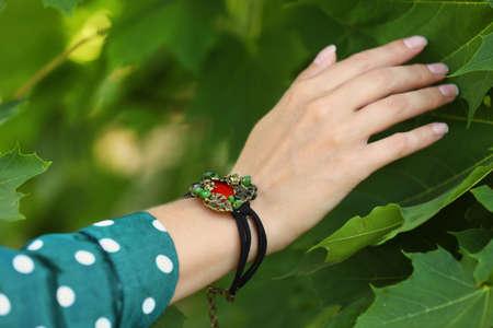 Young woman wearing beautiful metal bracelet with carnelian and gemstones outdoors, closeup