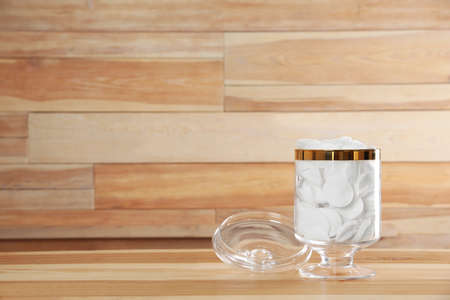 Decorative glass jar with cotton pads on table against wooden background. Space for text 写真素材