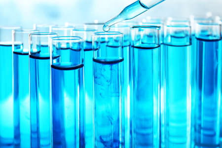 Dropping sample into test tube with blue liquid, closeup