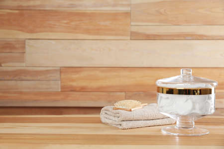 Decorative glass jar with cotton pads, towel and hairbrush on table against wooden background. Space for text 写真素材