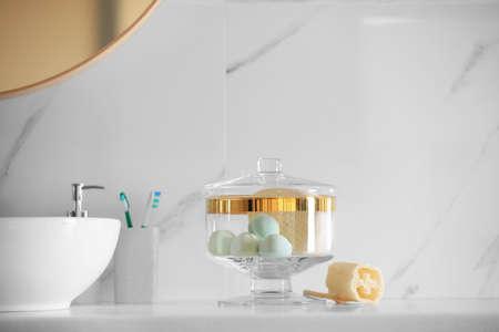 Jar with bath bombs and bath sponge on white countertop indoors 写真素材