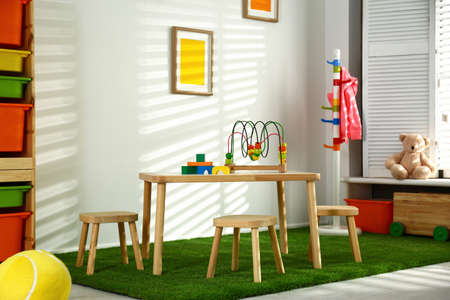 Stylish playroom interior with wooden table and stools 免版税图像