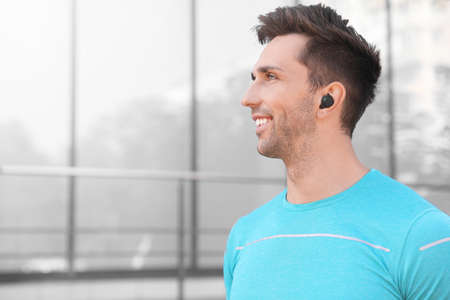 Young sportsman with wireless earphones on city street