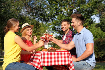 Group of people having picnic at table in park on summer day