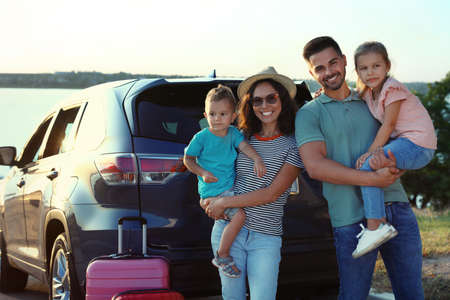 Happy family with suitcases near car on riverside