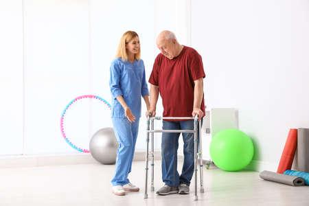 Custode che aiuta un uomo anziano con il deambulatore al chiuso Archivio Fotografico