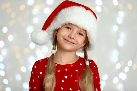 Happy little child in Santa hat against blurred festive lights. Christmas celebration