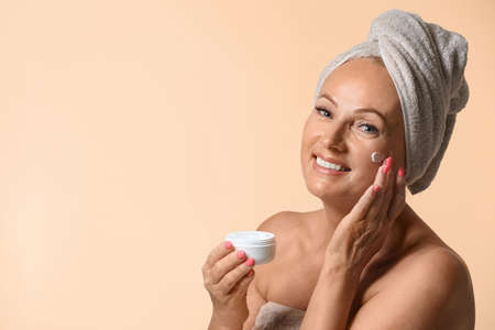 Portrait of beautiful mature woman with perfect skin holding jar of cream on beige background. Space for text Фото со стока