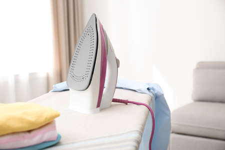 Board with modern iron and clean clothes indoors. Laundry day