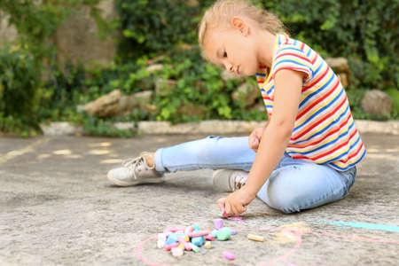 Upset little left-handed girl drawing with chalk on asphalt Banque d'images - 131695754