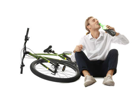 Depressed young man with bottle of wine near bicycle on white background Фото со стока