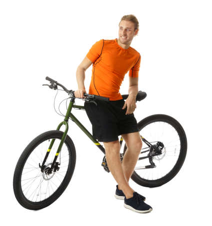Young man in sportswear with bicycle on white background