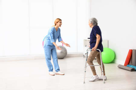Caretaker helping elderly woman with walking frame indoors