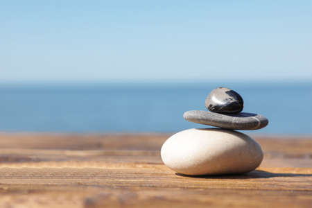 Stack of stones on wooden pier near sea, space for text. Zen concept Stock Photo