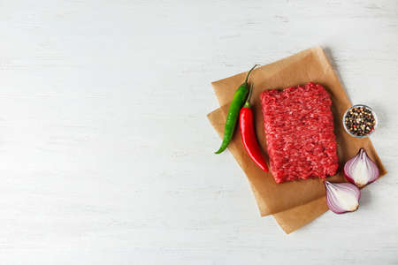 Fresh raw minced meat on white wooden table, top view. Space for text