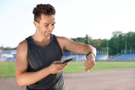Young sportsman with wireless earphones, mobile phone and smartwatch at stadium