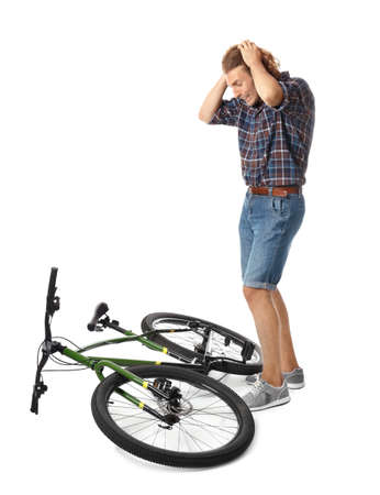 Emotional young man with bicycle on white background