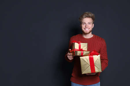 Young man with Christmas gifts on dark background. Space for text