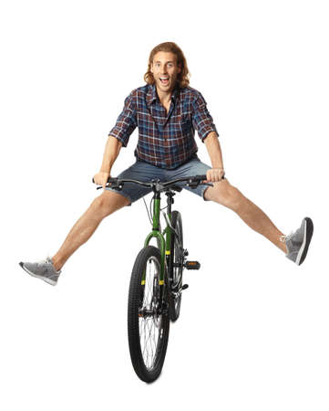 Happy young man riding bicycle on white background Фото со стока