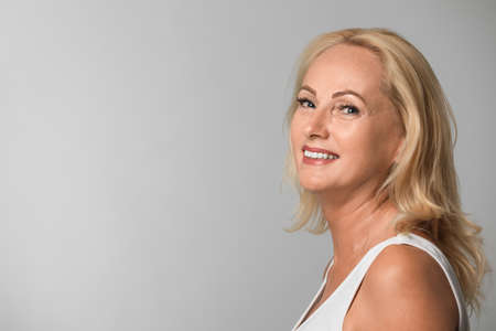 Portrait of beautiful mature woman with perfect skin on grey background. Space for text