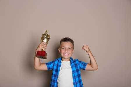 Happy boy with golden winning cup on beige background Фото со стока