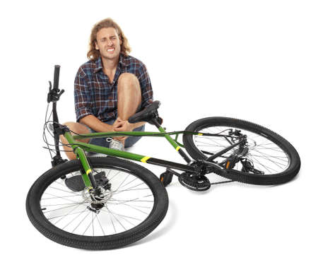 Young man with injured leg near bicycle on white background Фото со стока