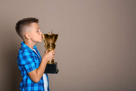 Happy boy kissing golden winning cup on beige background. Space for text