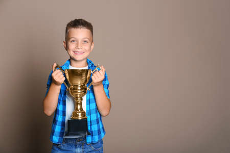 Happy boy with golden winning cup on beige background. Space for text