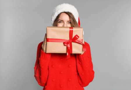 Happy young woman in Santa hat and sweater with gift box on light grey background. Christmas celebration