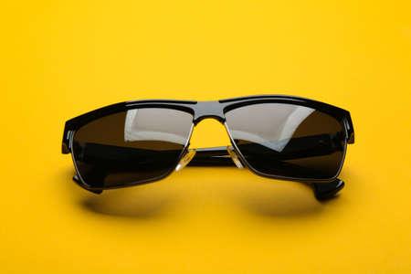 Stylish sunglasses on yellow background. Fashionable accessory Stock Photo