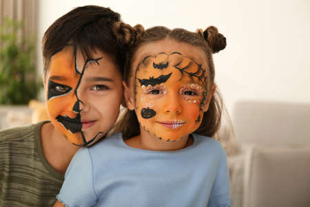 Cute little children with face painting indoors