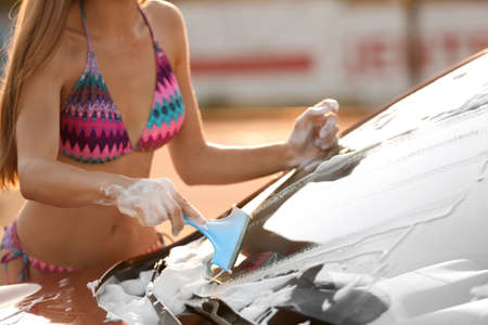 Young woman in swimsuit washing windshield of car with squeegee outdoors, closeup Banque d'images - 131310327