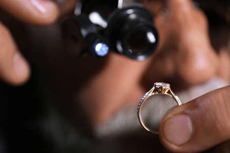 Male jeweler examining diamond ring in workshop, closeup view 版權商用圖片