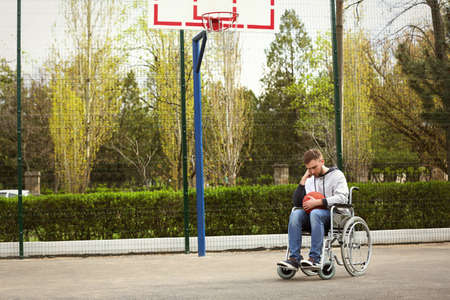 Upset man in wheelchair with ball on sports ground Banco de Imagens