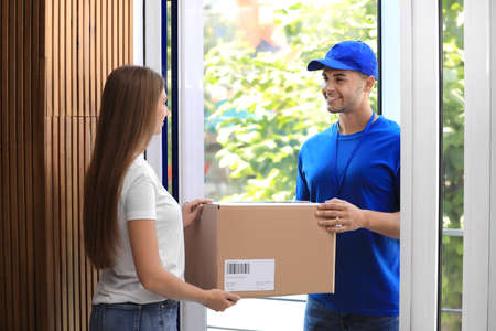 Woman receiving parcel from courier on doorstep