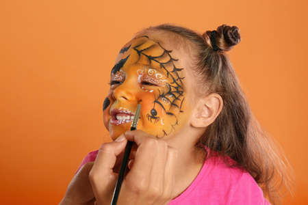 Artist painting face of little girl on orange background