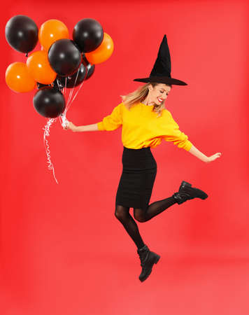 Beautiful woman wearing witch costume for Halloween party jumping with balloons on red background 版權商用圖片