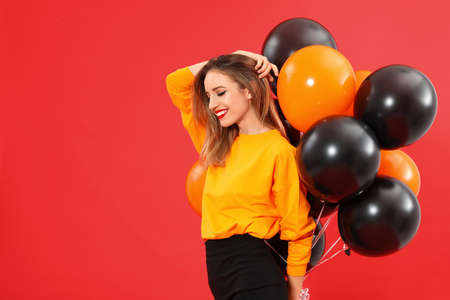 Beautiful woman with balloons on red background, space for text. Halloween party