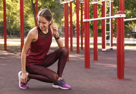 Young woman with wireless headphones listening to music on sports ground. Space for text 版權商用圖片