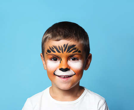 Cute little boy with face painting on blue background