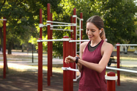 Young woman with wireless headphones and smartwatch listening to music on sports ground 版權商用圖片