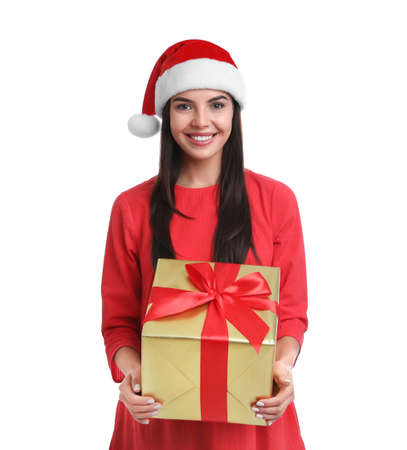 Happy young woman in Santa hat holding Christmas gift on white background