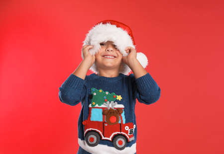 Happy little child in Santa hat on red background. Christmas celebration