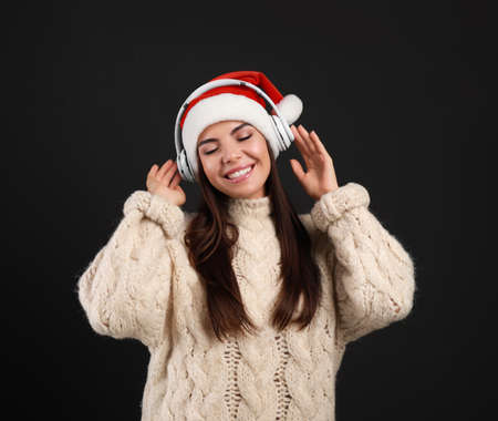 Young woman in Santa hat listening to Christmas music on black background